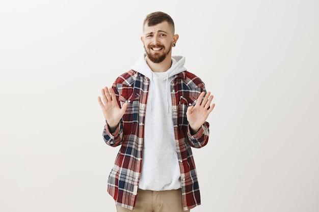 Ragazzo hipster imbarazzante che rifiuta l'offerta, si stringe la mano in segno di rifiuto e fa un sorriso forzato