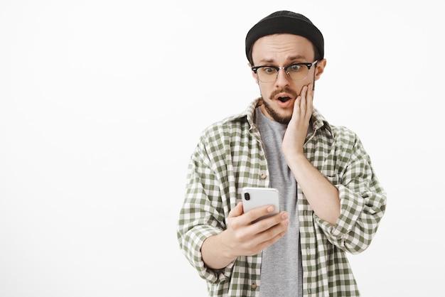 Ragazzo impopolare scioccato riceve mi piace sotto l'ultimo post nel social network senza fiato con la bocca aperta tenendo la mano sulla guancia fissando sorpreso e stupito lo schermo dello smartphone sul muro bianco