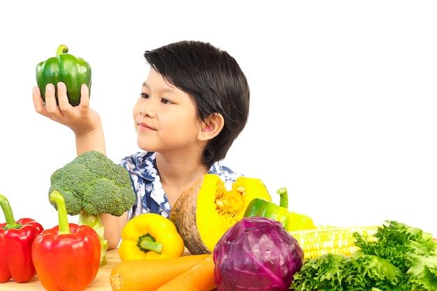 Ragazzo in buona salute asiatico che mostra espressione felice con la verdura variopinta fresca di varietà