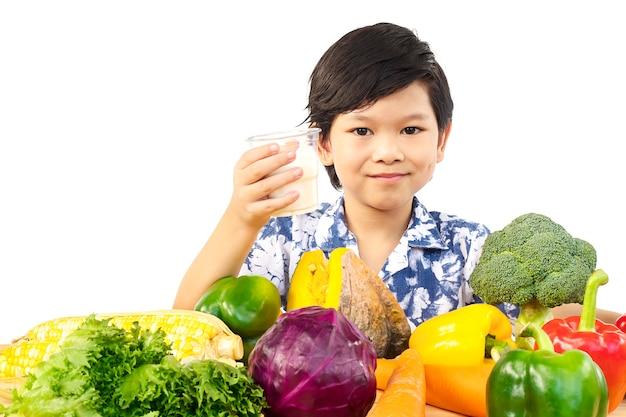 Ragazzo in buona salute asiatico che mostra espressione felice con un bicchiere di latte e varietà di verdure fresche