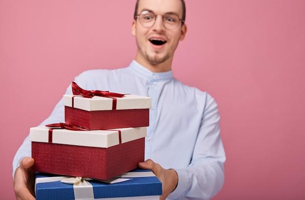Ragazzo in camicia tiene i regali con la bocca aperta a sorpresa