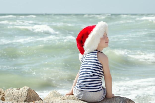 Ragazzo in cappello della santa e maglietta a strisce che si siede sulla spiaggia