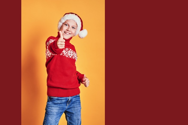 Ragazzo in cappello di santa e maglione rosso divertendosi e mostrando pollice su il giorno di natale contro il fondo giallo