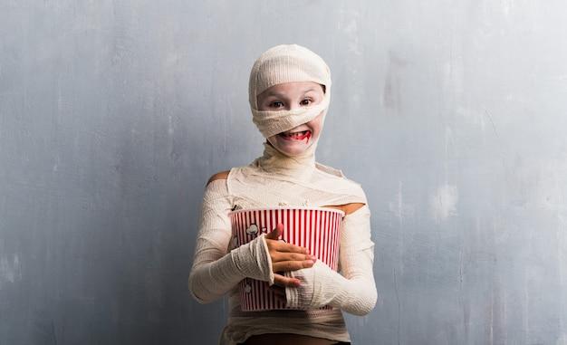 Ragazzo in costume della mummia che mangia i popcorn per le feste di halloween