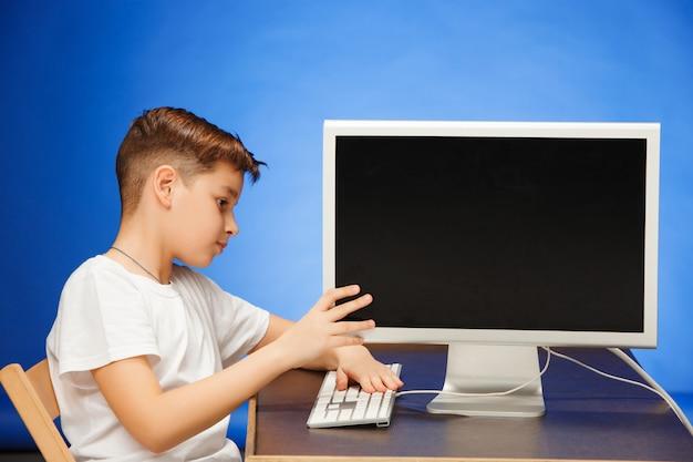Ragazzo in età scolare che si siede con il computer portatile del monitor allo studio