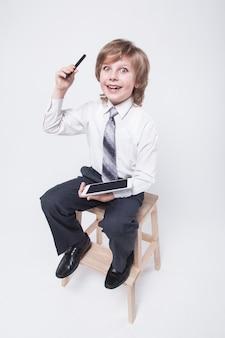 Ragazzo in giacca e cravatta in possesso di un tablet