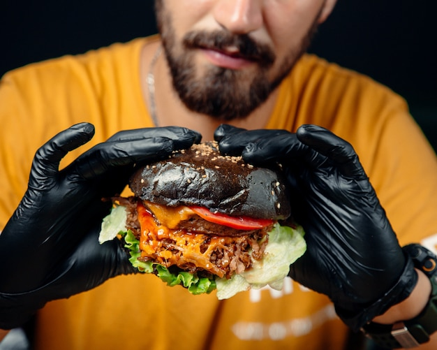 Ragazzo in guanti neri tiene un succoso cheeseburger nel pane nero