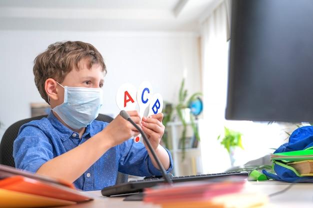 Ragazzo in maschera con il computer, facendo i compiti durante la quarantena di coronavirus