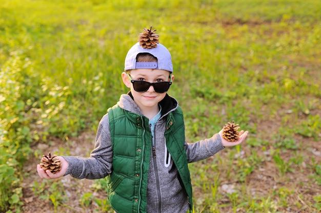 Ragazzo in occhiali da sole con dossi nelle sue mani e sulla sua testa contro la foresta.