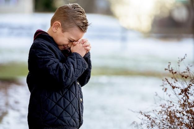 Ragazzo in piedi con gli occhi chiusi e pregando