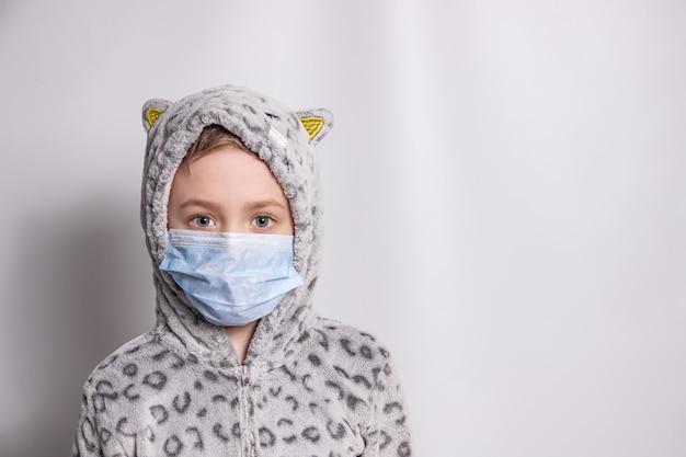 Ragazzo in pigiama e una mascherina medica su una luce
