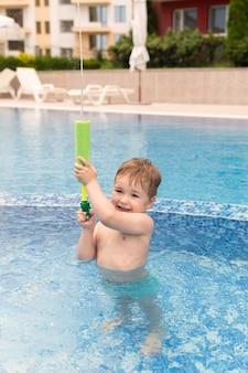 Ragazzo in piscina giocando con la pistola ad acqua