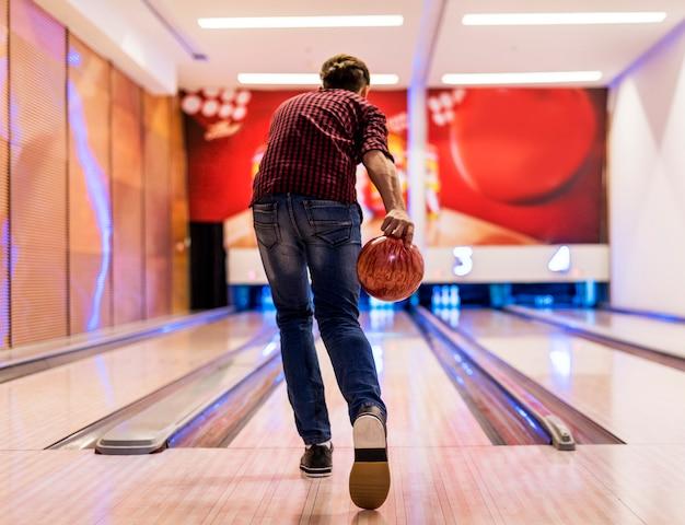 Ragazzo in procinto di lanciare un concetto di hobby e tempo libero di palla da bowling