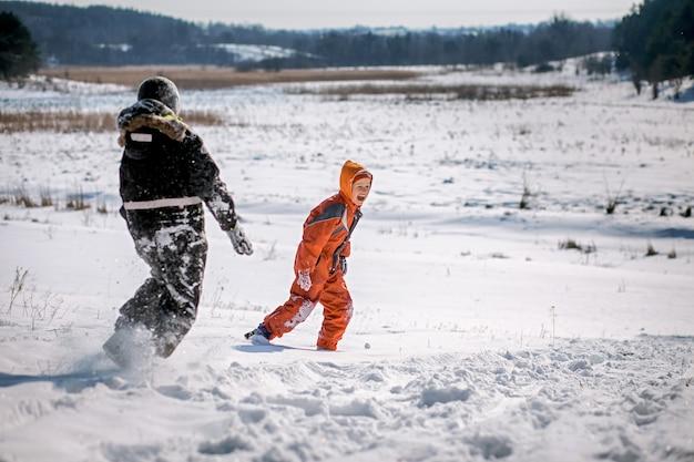 Ragazzo in tuta da sci sulla montagna di neve con la slitta
