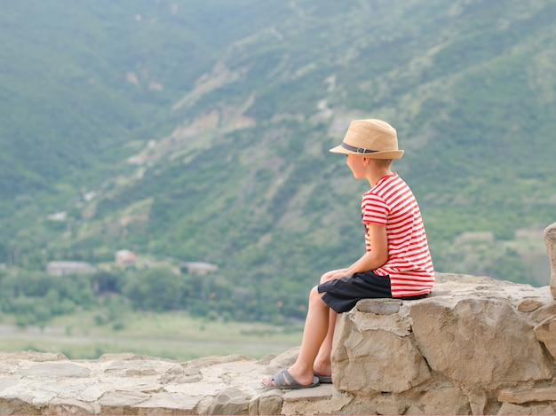 Ragazzo in un cappello che si siede sulle pietre