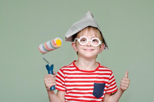 Ragazzo in un cappello di carta e occhiali mostra il fresco. ritratto. rullo per pittura