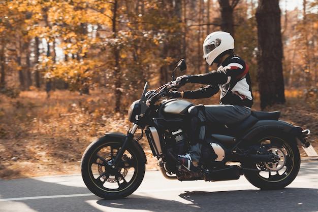 Ragazzo in un casco sta guidando su strada forestale.