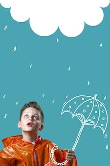 Ragazzo in un impermeabile arancione e con un ombrello dipinto sta sotto la pioggia