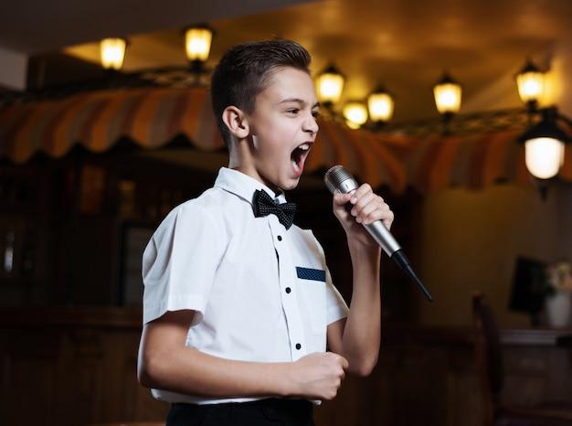 Ragazzo in una camicia bianca che canta nel microfono in un ristorante.