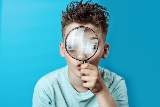 Ragazzo in una t-shirt leggera guardando in una grande lente di ingrandimento