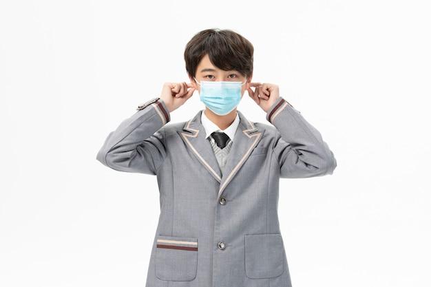 Ragazzo in uniforme scolastica che indossa maschera
