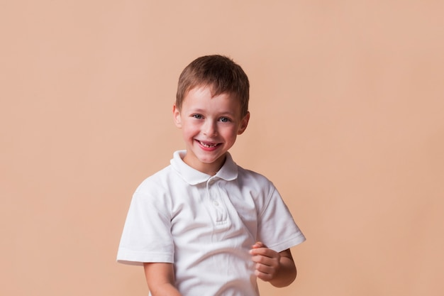 Ragazzo innocente sorridente su sfondo beige