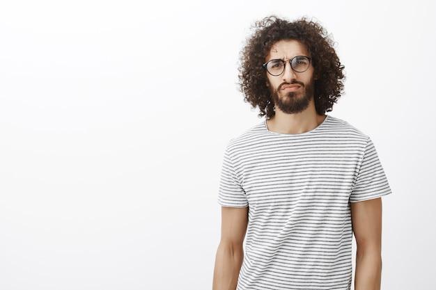 Ragazzo ispanico attraente premuroso sospettoso in occhiali alla moda, alzando un sopracciglio in dubbio e fissando