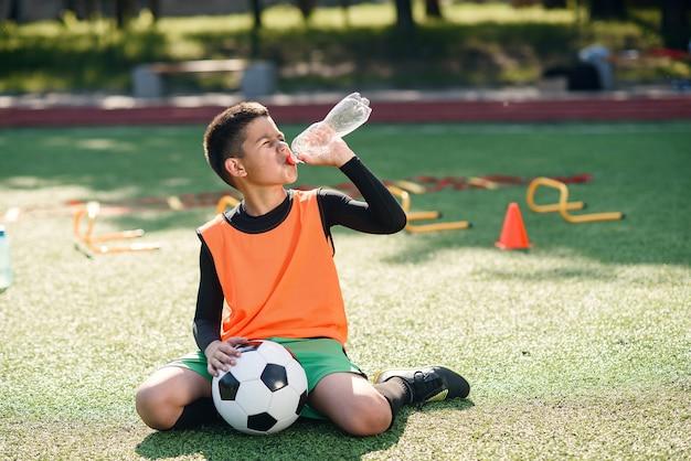 Ragazzo ispanico stanco in uniforme di calcio beve l'acqua dalla bottiglia di plastica dopo un allenamento intensivo