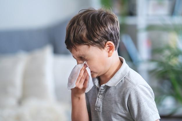 Ragazzo malato che soffia il naso nel tessuto, bambino malsano che soffre di naso che cola