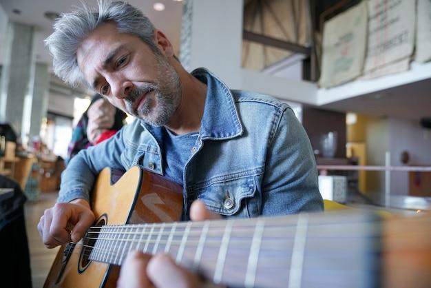 Ragazzo maturo alla moda che suona la chitarra in un bar