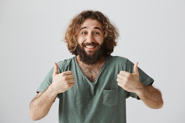 Ragazzo mediorientale felice eccitato che mostra sostegno, pollice in su in approvazione