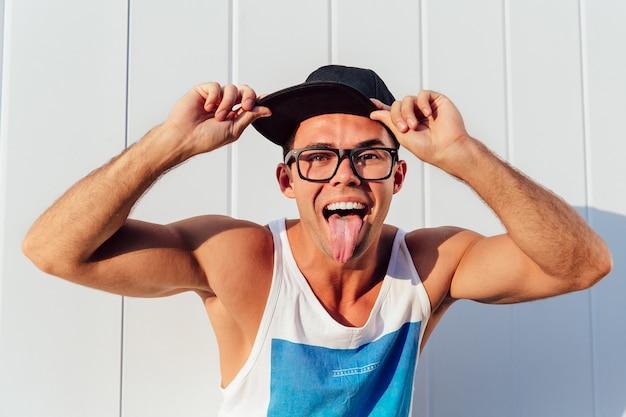 Ragazzo muscoloso allegro in occhiali e berretto mostrando una lingua a porte chiuse