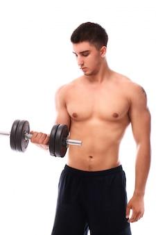 Ragazzo muscoloso che lavora con manubri