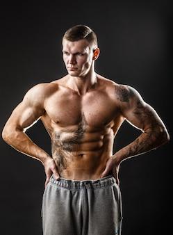 Ragazzo muscoloso con tatuaggio. isolato su sfondo scuro