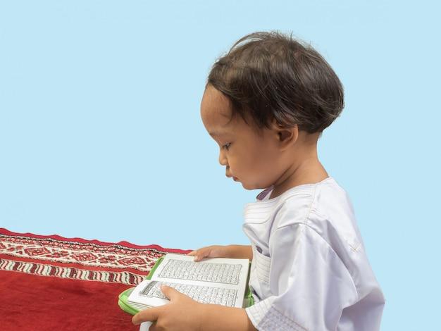 Ragazzo musulmano in un vestito che legge il corano