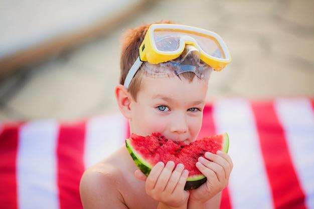 Ragazzo negli occhiali di protezione di immersione subacquea che mangia anguria che si siede sull'asciugamano di spiaggia rosso e bianco
