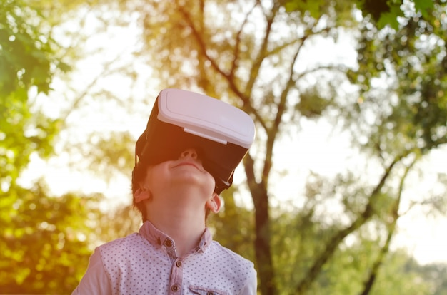 Ragazzo nel casco della realtà virtuale contro la superficie della natura