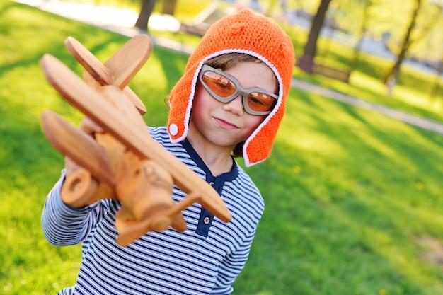 Ragazzo nel pilota arancio del casco che gioca in aereo di legno del giocattolo contro erba