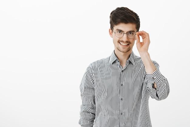 Ragazzo nerd civettuolo con occhiali rotondi con barba e baffi, che tiene il bordo degli occhiali e sorride ampiamente, sentendosi sicuro e rilassato dopo aver detto di riprendere la linea alla ragazza attraente al bar