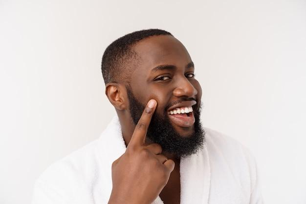 Ragazzo nero che indossa un dito puntato accappatoio con sorpresa ed emozione felice. isolato su bianco.