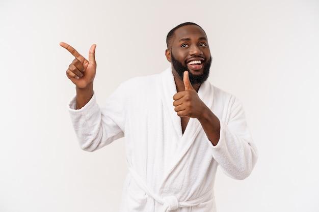 Ragazzo nero che indossa un dito puntato accappatoio con sorpresa ed emozione felice.