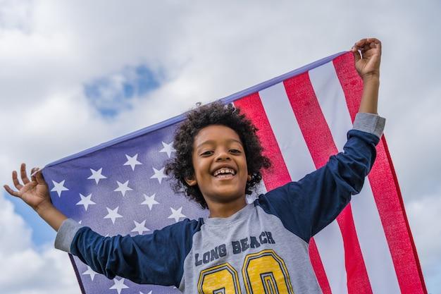 Ragazzo nero con i capelli afro e una bandiera americana che celebra la festa dell'indipendenza degli stati uniti