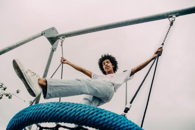 Ragazzo nero in piedi su un grande swing