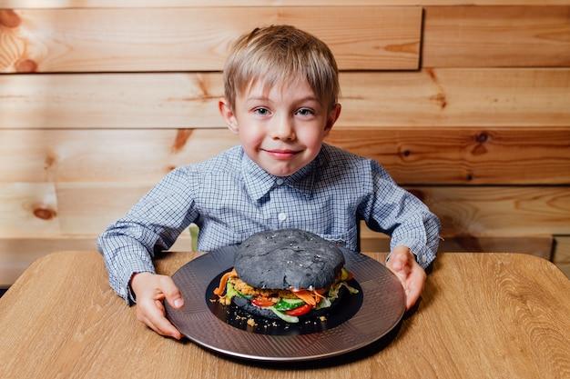 Ragazzo piccolo bambino con hamburger nero vegetariano