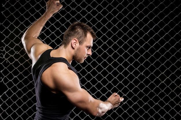 Ragazzo potente che mostra i suoi muscoli sul recinto