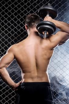 Ragazzo potente con manubri che mostrano i muscoli sul recinto