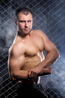 Ragazzo potente con una catena che mostra i suoi muscoli