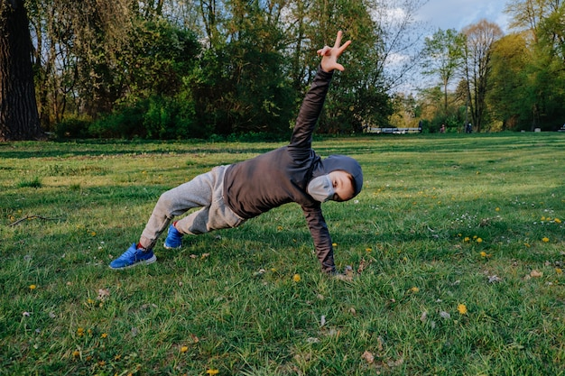 Ragazzo ragazzo che indossa come ninja fa diversi esercizi all'aperto