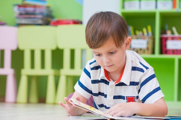 Ragazzo ragazzo si sdraiò sul pavimento e leggendo un libro di favole