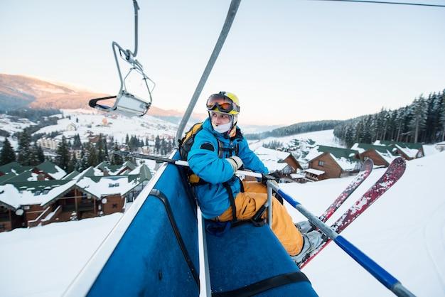 Ragazzo sciatore seduto alla seggiovia di sci in bella giornata e torna indietro. avvicinamento. concetto di sci.